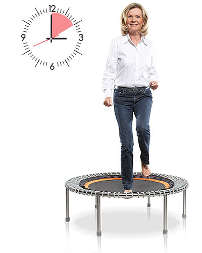 A woman exercises on a bellicon® mini trampoline and behind her a clock is depicted