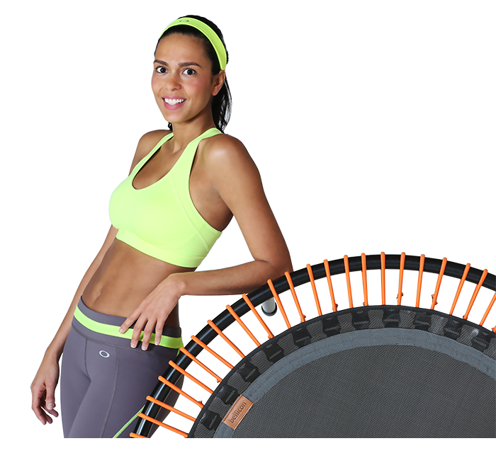 A woman stands smiliing while leaning on an upright bellicon® mini trampoline