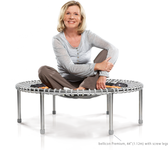 An older woman sits smiling on a bellicon® mini trampoline
