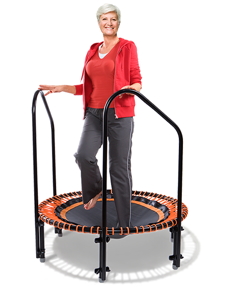 A woman of about 70 exercising with support hand bars on a bellicon® mini trampoline