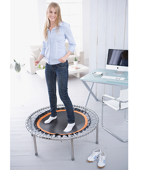 A woman in an office stands smiling on a bellicon® mini trampoline