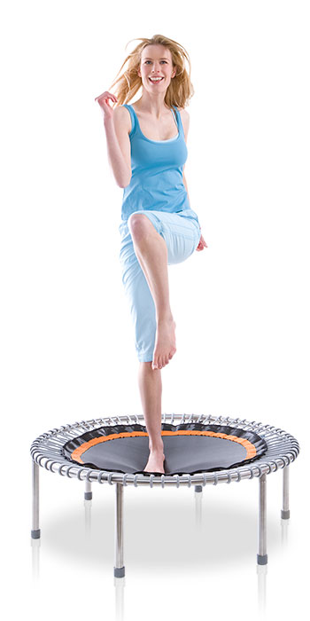 A young blonde woman doing knee up exercises on a bellicon® mini trampoline