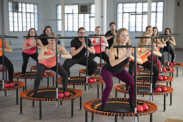 Foto de un entrenamiento de grupo bellicon Bounce haciendo un squat sobre bellicon® Plus