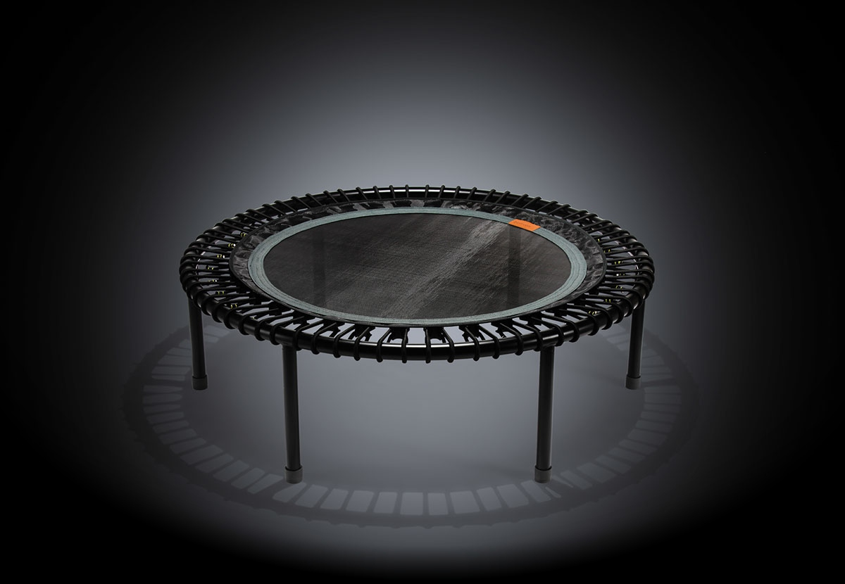 A black and gray bellicon® mini trampoline with a script 'we bring out the champion in you' above it