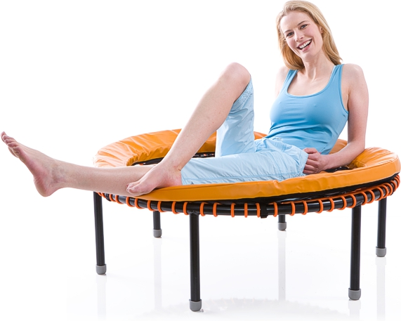A woman lies smiling on a bellicon® mini trampoline equiped with a frame cushion