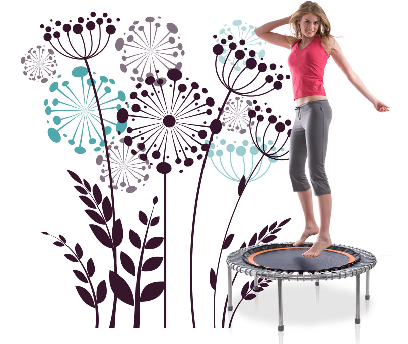 A young woman exercises on a bellicon® trampoline before a floral background