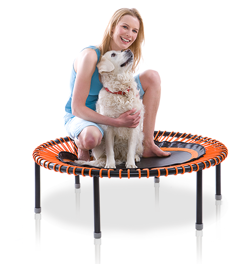 A young woman with a dog sits on a bellicon® mini trampoline