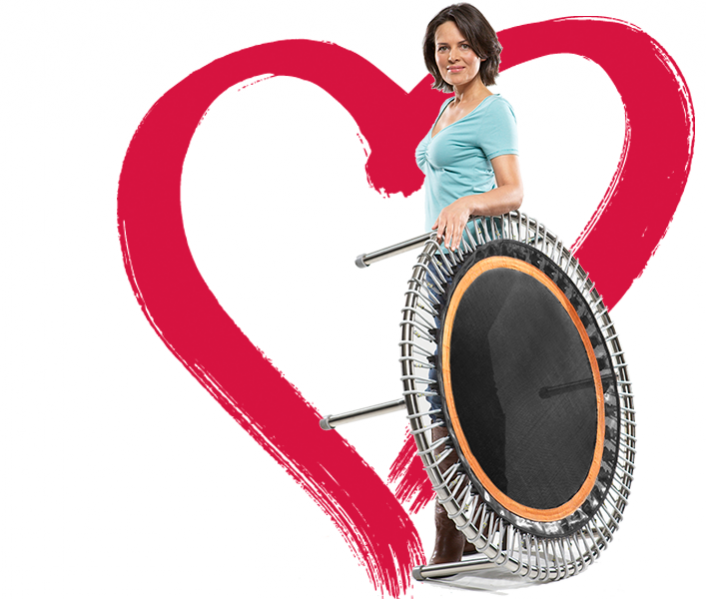A woman stands next to an upright bellicon® mini trampoline before a background of a large red heart