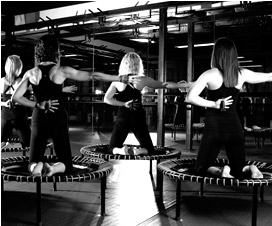 A picture of a class of particants kneeling on bellicon® trampolines in a studio