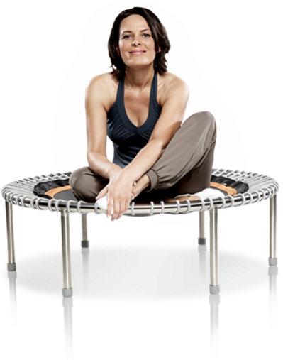 A woman sits smiling on a bellicon® premium mini trampoline