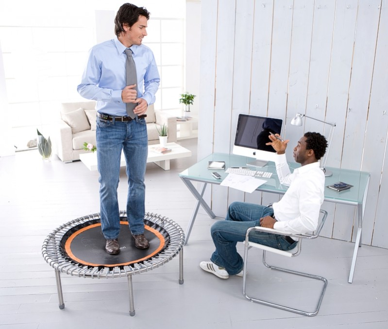 Two colleagues talking in an office while one stands on a bellicon® mini trampoline