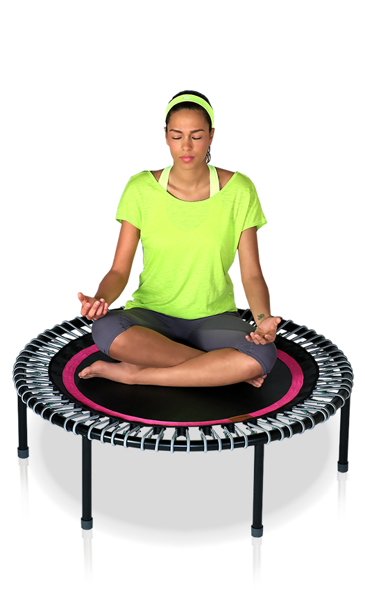 A woman sits meditating cross legged on a bellicon® mini trampoline