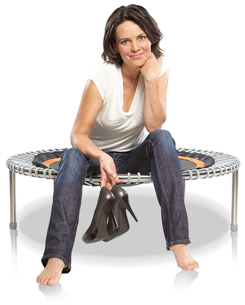 A woman holding her high heels in hand sits smiling on a bellicon® mini trampoline