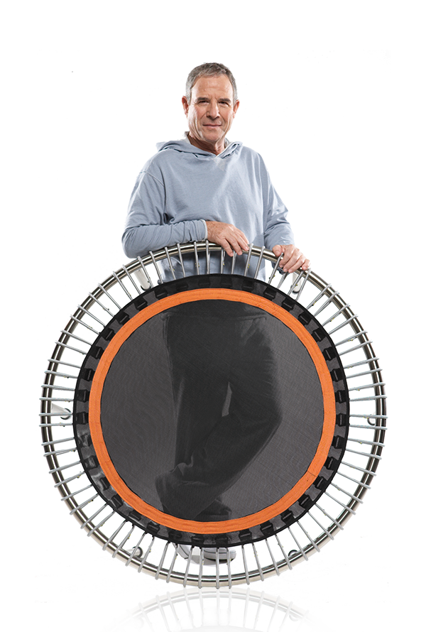 An older man stands behind an upright bellicon® mini trampoline